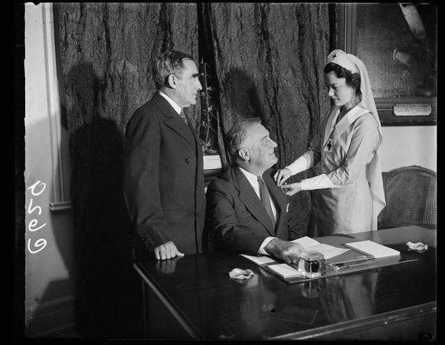 CHIEF EXECUTIVE ANSWERS RED CROSS ROLL CALL. WASHINGTON, D.C. OCTOBER 20. PRESIDENT ROOSEVELT ANSWERED THE AMERICAN RED CROSS 1937 ROLL CALL TODAY AND WAS ENROLLED BY MISS HEBE REYNOLDS, OF THE DISTRICT OF COLUMBIA RED CROSS CHAPTER, AT THE WHITE HOUSE. MISS REYNOLDS IS THE DAUGHTER OF MAJ. GEN. CHARLES R. REYNOLDS, SURGEON GENERAL OF THE U.S. ARMY. ON THE LEFT IS ADMIRAL CARY T. GRAYSON, CHAIRMAN OF THE AMERICAN RED CROSS