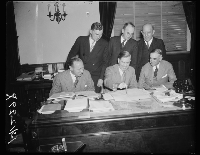 """Crop Insurance Committee meets for first time. Washington, D.C. Sept. 25. Secretary of Agriculture Henry A. Wallace, as chairman called the crop insurance committee appointed by President Roosevelt this week into session today for the first time. The first thing the committee will consider, Wallace said, is on what crops the first """"experiment"""" in crop insurance should be made. n the picture, left to right; (front row) Wayne C. Taylor; Assistant Secretary of the Treasury; Secretary Wallace; and Ernest G. Draper, Assistant Secretary of Commerce. In the rear, left to right: Roy M. Green, Bureau of Agricultural Economics; Dr. A.G. Black, chief, Bureau of Agricultural Economics; and H.R. Tolley, Administrator, AAA"""