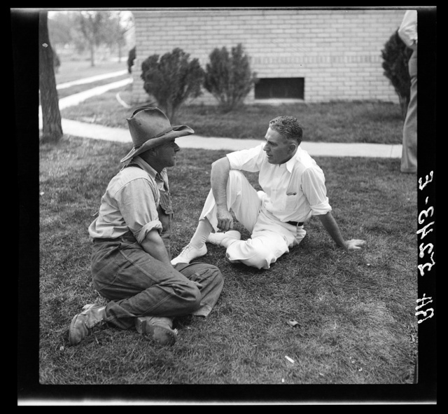Dr. Tugwell confers with farmer on lawn of courthouse. Springfield, Colorado
