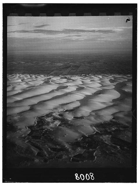Egypt. En route to Luxor. A sea of sand in Upper Egypt; showing marked line of cultivated area in semi-distance