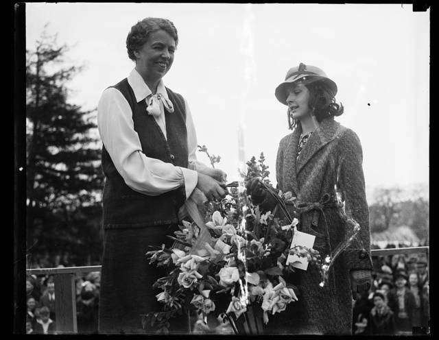 FLOWERS FOR FIRST LADY. WASHINGTON, D.C. APRIL 13. DORIS THORNE, ACTING FOR THE GOOD SAMARITANS, A CHARITABLE ORGANIZATION, PRESENTS A BASKET OF FLOWERS TO MRS. FRANKLIN ROOSEVELT. THIS WAS PART OF THE COLORFUL EASTER EGG ROLLING CEREMONIES ON THE WHITE HOUSE LAWN