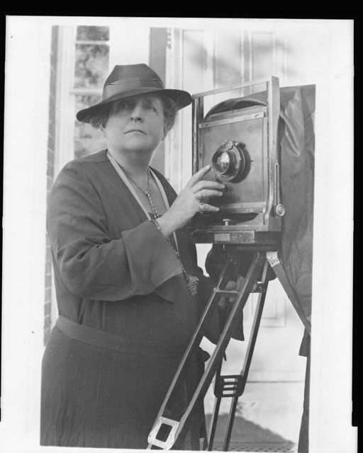 [Frances Benjamin Johnston, 1864-1952, half length, facing front, adjusting lens of large tripod camera, in front of the Arts Club, 2017 Eye Street, Washington, D.C.]