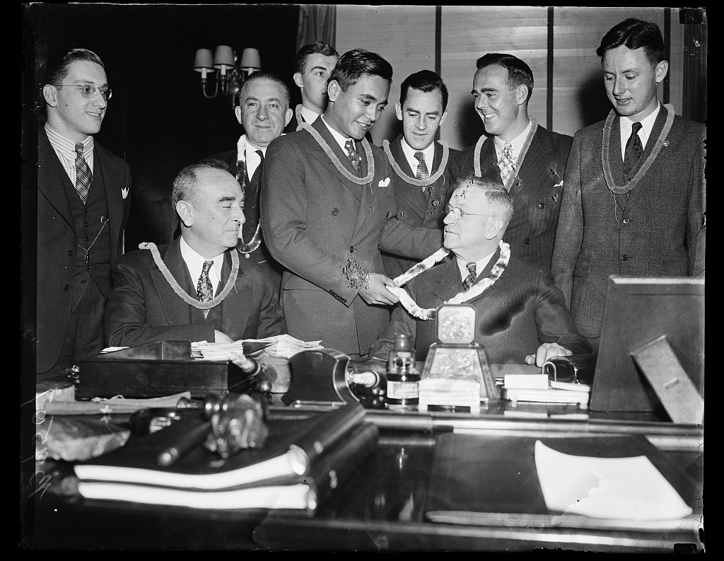 [Harold Ickes wearing lei, at desk with group; Samuel Wilder King, Delegate from Hawaii to House of Representatives, seated at left. Washington, D.C.]