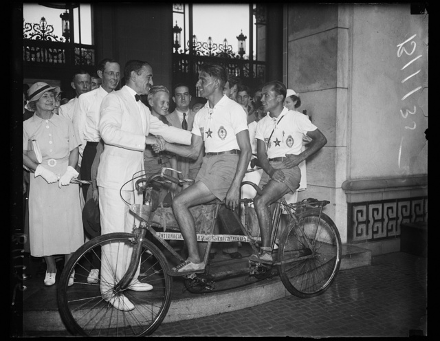 """In a bicycle built for two,"" Washington, D.C. September 8. Dr. Loo S. Rowe greets Victor Scarraffia and Vincente Gregori ? (front to rear) two Argentinian cyclists who left Buenos Aires January 1, 1934 in their bicycle. After two years and a half of privations which included being lost in the desert, attacks of tropical fever, etc., they have finally completed their ""goodwil visit."" Doctor Rowe is the Director General of the Pan-American Union"