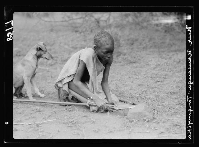 Kenya Colony. Namanga, southern game reserve. Native boy sharpening his spear