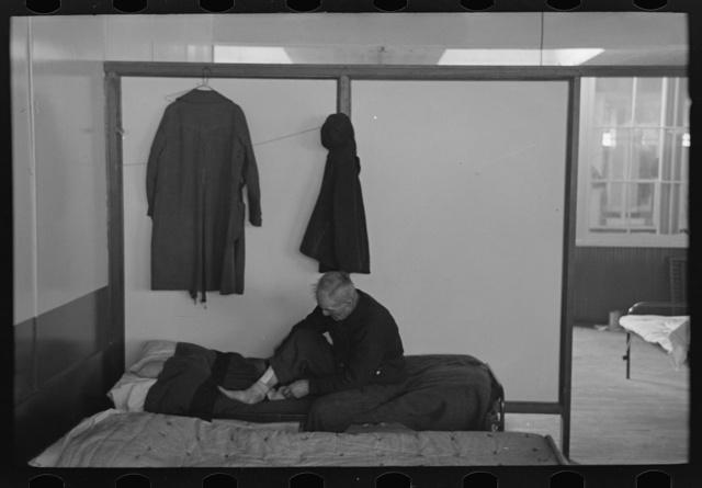 Man examining ankle, homeless men's bureau, Sioux City, Iowa