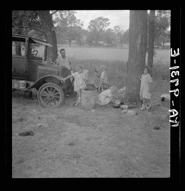 Migrant family from Oklahoma in Texas. A family of six alongside the road. An example of how they fall between the relief agencies. The father, aged thirty-five, is an intelligent fellow, a painter by trade. Advanced tuberculosis, victim of an occupational disease. Ineligible for WPA  (Works Progress Administration), rated as totally disabled. As a state charge under Oklahoma relief standards, the family were told the maximum relief would be seven dollars every two weeks. They lost their home, their furniture, took to the road a year ago and when the photographs were made they were found to be without money, shelter, and without food for the four children