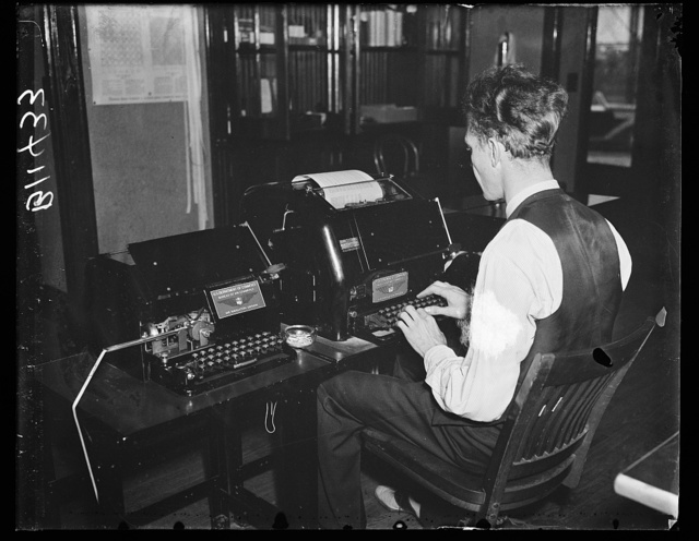 """New wireless teletypewriter. Washington, D.C., Oct. 15. A new radio teletypewriter service permitting instantaneous transmission of written records without the aid of wires, has been perfected by the experts of the Bureau of Air Commerce, Department of Commerce. Commerce officials said a chain of teletypewriters could be operated by radio at """"great distances"""" and even in an airplane in flight. In this picture the new machine is being operated by R.B. Ladd, at the Bureau of Air Commerce field at Silver Hill, MD"""