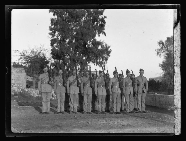 """Palestine disturbances 1936. Royal Engineers """"observers"""" in the beam of light which is being played on the city and country-side"""