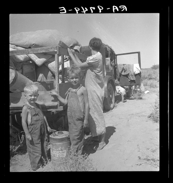 "Part of an impoverished family of nine on a New Mexico highway. Depression refugees from Iowa. Left Iowa in 1932 because of father's ill health. Father an auto mechanic laborer, painter by trade, tubercular. Family has been on relief in Arizona but refused entry on relief roles in Iowa to which state they wish to return. Nine children including a sick four-month-old baby. No money at all. About to sell their belongings and trailer for money to buy food. ""We don't want to go where we'll be a nuisance to anybody"""