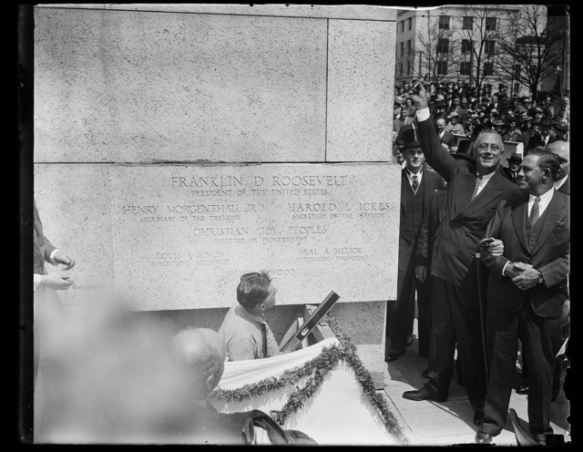 PRESIDENT ROOSEVELT AT CORNERSTONE CEREMONIES. WASHINGTON, D.C. APRIL 16. PRESIDENT ROOSEVELT WAS IN A HAPPY MOOD TODAY AS HE ATTENDED THE LAYING OF THE CORNERSTONE CEREMONIES OF THE NEW $12,000,000 INTERIOR BUILDING. THE PRESIDENT IS HOLDING THE THE TROWEL USED BY GEORGE WASHINGTON WHEN HE LAYED THE CORNERSTONE OF THE U.S. CAPITOL IN 1793