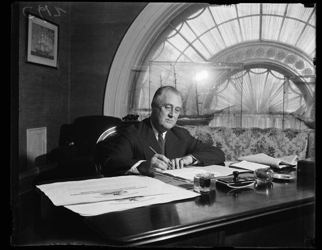 PRESIDENT SIGNS BILLS. WASHINGTON, D.C. JUNE 8. PRESIDENT FRANKLIN ROOSEVELT SIGNS A NUMBER OF BILLS AND PUTS FINISHING TOUCHES ON HIS SPEECHES BEFORE LEAVING WASHINGTON FOR HIS SOUTHERN TRIP. THIS PHOTOGRAPH WAS MADE IN THE EAST HALL OF THE WHITE HOUSE