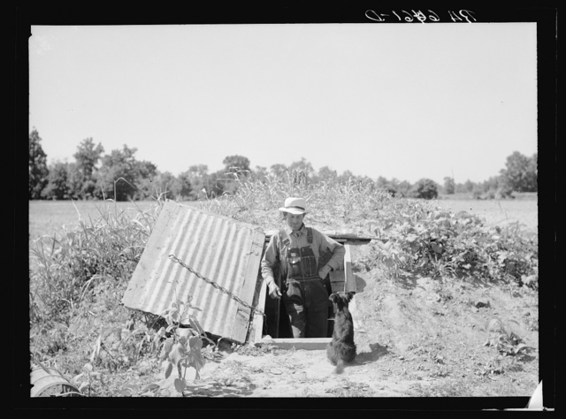 Rehabilitation Administration client standing in opening of storm cellar which is used also to store hundreds of cans of food. Near Batesville, Arkansas