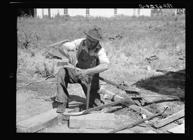 Repairing a plow on farm. Near West Memphis. Tennessee