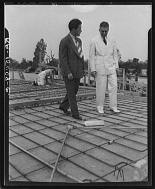 Resettlement Administrator R.G. Tugwell examines foundations of houses under construction at Greenbelt, Maryland. With him is Wallace Richards, coordinator of the Greenbelt project