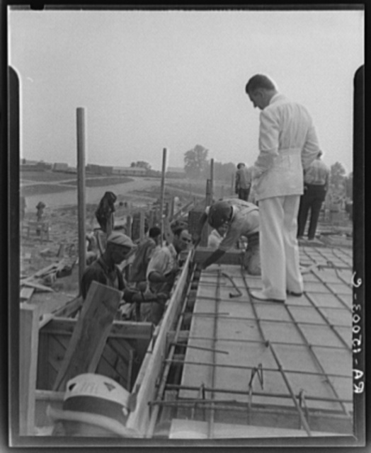 Resettlement Administrator R.G. Tugwell examines foundations of houses under construction at the Greenbelt project, Maryland