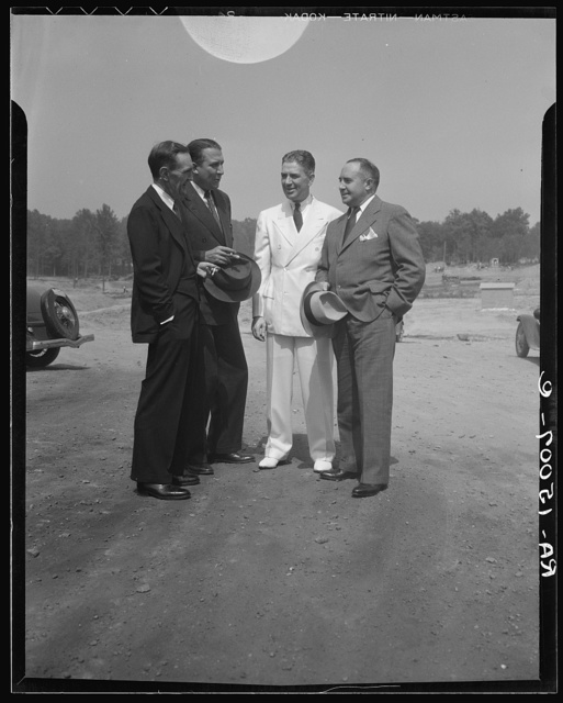 Resettlement Administrator R.G. Tugwell (in white), with his aides John O. Walker, John L. Lansill, and Frank Schmidt, inspects progress made at Greenbelt, Maryland, one of the three model communities which the RA (Resettlement Administration) is building to demonstrate that good homes in lovely surroundings can be within reach of city families with only moderate incomes