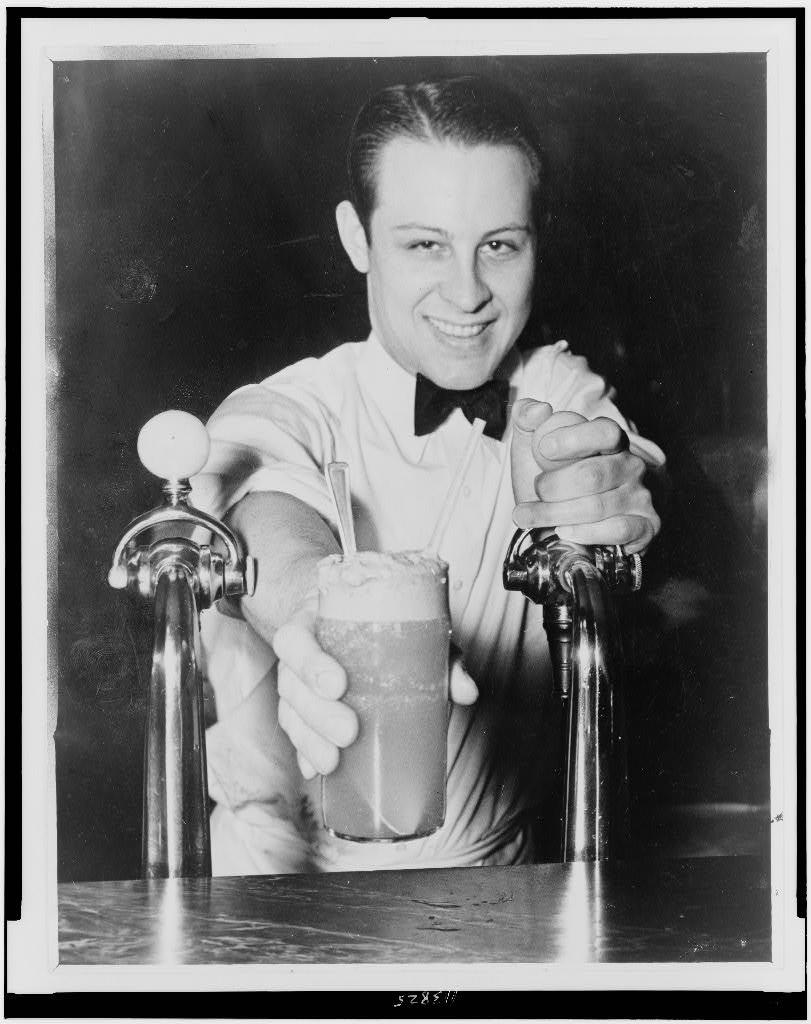 """[""""Soda jerk"""" passing ice cream soda between two soda fountains] / staff photo by Alan Fisher."""