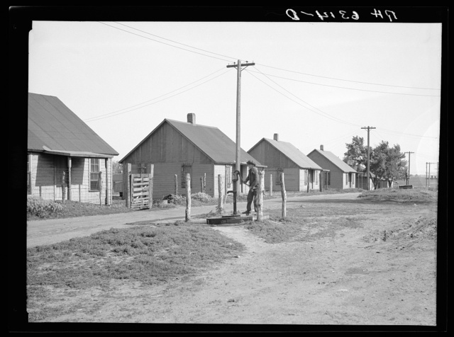 Street scene in the mining settlement of Zookspur, Iowa, where part of the occupants of the Granger Homestead formerly lived. Each pump services four houses. Rent four dollars per month