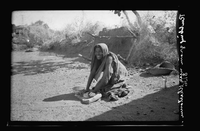 "Sudan. Khartoum. Dain el-Tashy woman ""rubbing"" grain, primitive method of grinding cereals"