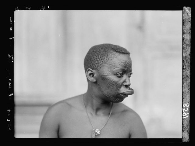 Tanganyika. Dar-es-Salem. Native woman. Close up. Patterned face and extended upper lip