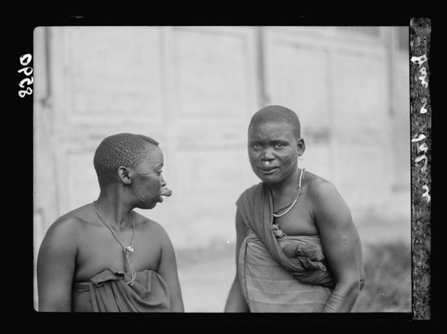 Tanganyika. Dar-es-Salem. Native women with cicatrice patterns on their faces and buttons inserted in upper lips