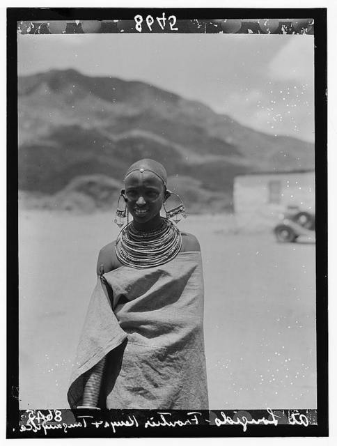 Tanganyika. En route to Longido. A girl with large ear decorations and quantities of neck rings, with arms covered with cloak