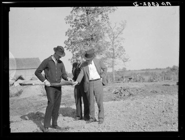 The Farm Security Administration supervisor shows the creditor the type of soil on the farm of the Farm Security Administration client. The rehabilitation supervisor stands by. Monroe County, Iowa