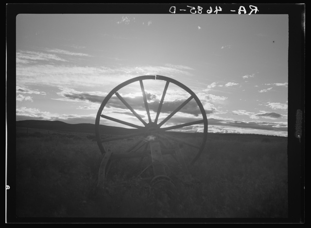 The sun sets on a broken wagon wheel, symbolic of the vain efforts to farm on the dry arid land of central Oregon