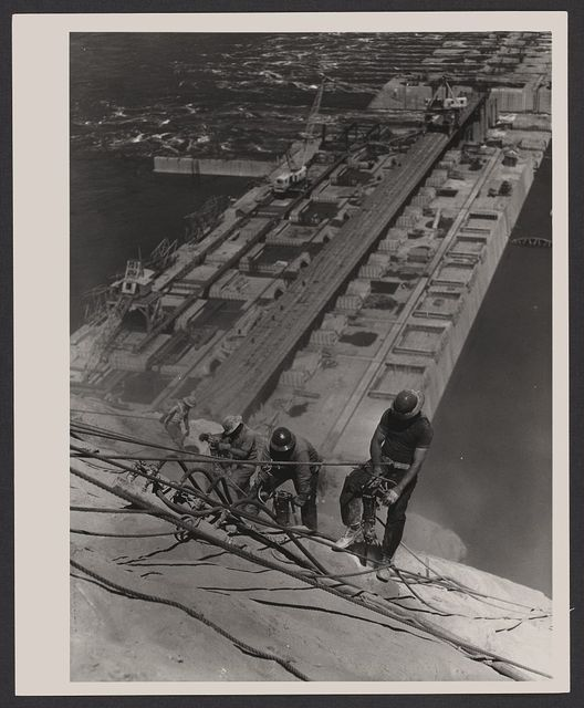 [Three construction workers, suspended by ropes, with pneumatic hammers cutting into a wall or mountain, during construction of the Grand Coulee Dam, Columbia River, Washington]