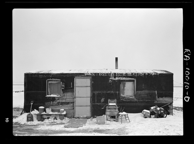 Three-room shack, the residence of L.H. Nissen, hired man for a tenant farmer. Farm is owned by a loan company. Ten people live in the shack: mother, father, seven children, and one grandchild. Iowa
