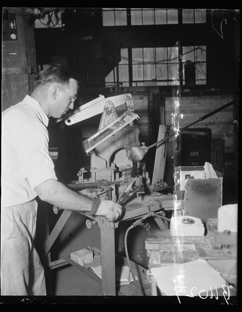 Uncle Sam makes own glass. Washington, D.C. Aug. 24. All optical glass used by the United States Navy is manufactured and finished by the Bureau of Standards in Washington. L. Maxwell, of the Glass Section, Bureau of Standards, is shown cutting molten glass into the mold. He uses ordinary tailor's shears in cutting the hot substance which is about as soft as hot molasses candy