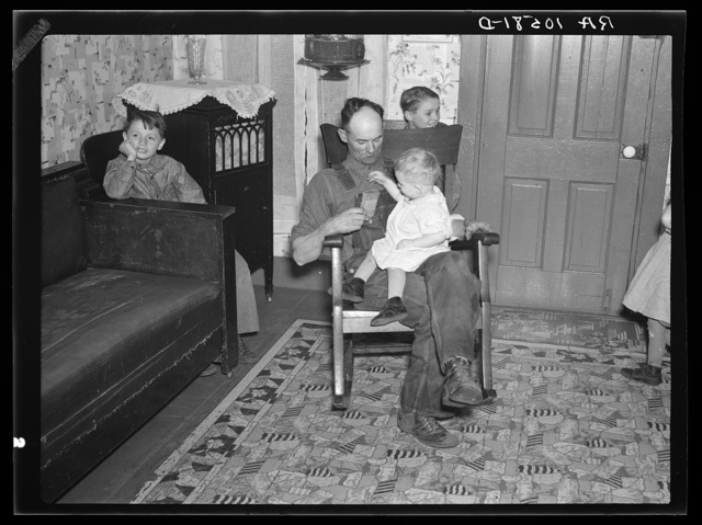 7:40 p.m. Tip Estes, hired man, with the youngest of his nine children. After dinner the family sits around until 8:00 or 8:30, when they go to bed. There is no reading matter in the house