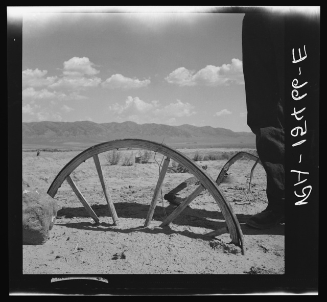 A brief cloudburst buries a wagon wheel to the axle as water erosion strips barren grazing land. On the Idaho land use project