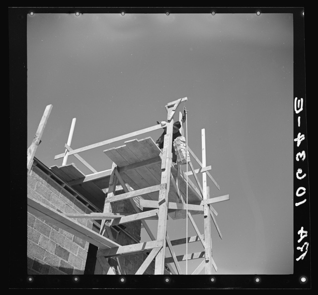 A load of brick going up the building chimney of a house under construction at Greendale, Wisconsin