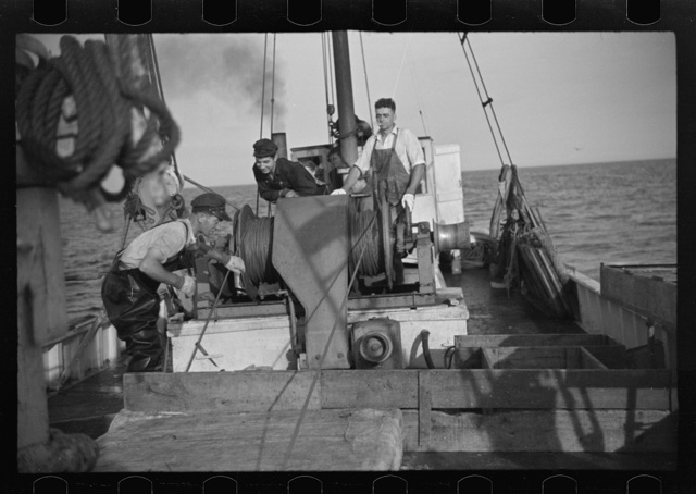 """Aboard a trawler (locally called a dragger). The power-driven winch lets out the starboard net. While over fishing grounds one of two nets is constantly in the water, dragging along the bottom. Boats are powerful, diesel-engined, between forty and seventy-five feet long. Their unrestricted use has done much to cause the """"fish-famine"""" along this coast because nets bring up everything, fish, minnows and even spawn. Provincetown, Massachusetts"""