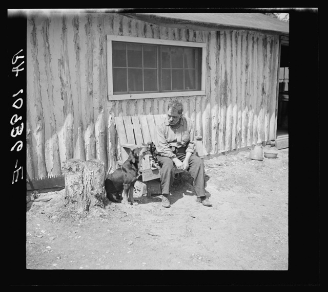 Black Aleck Dickinson and his dog Snoop. Dickinson is a single shacker in Iron County, Michigan