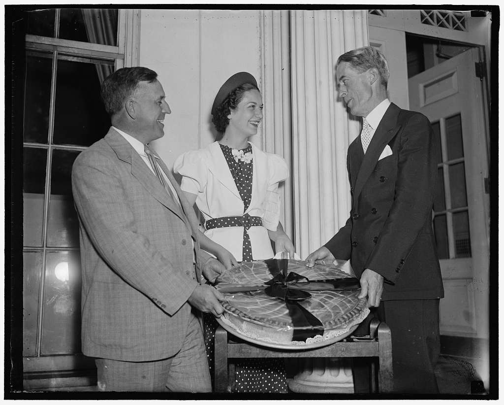 Cherry pie for the President. Washington D.C. July 8. The cherry queen of the National Cherry Festival Miss Eliene Lyon, of Traverse City, Mich. Today presented to the president this huge cherry pie. The pie was received for the President by his secretary Marvin McIntyre, on the left is Senator Prentiss Brown of Michigan, who accompanied Miss Lyon to the White House