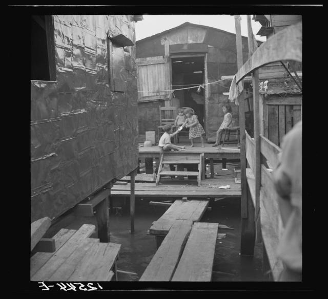 "Children in the workers' quarter of Puerto de Tierra. Note the water of the tidal swamp under the houses and ""sidewalk."" San Juan, Puerto Rico"