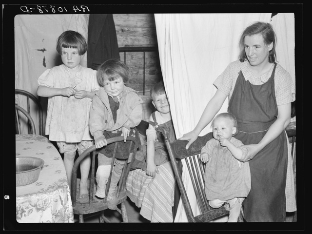Children of Mrs. Bodray's daughter in their shack near Tipler, Wisconsin. A sheet separates the front part of their one-room shack from the rear