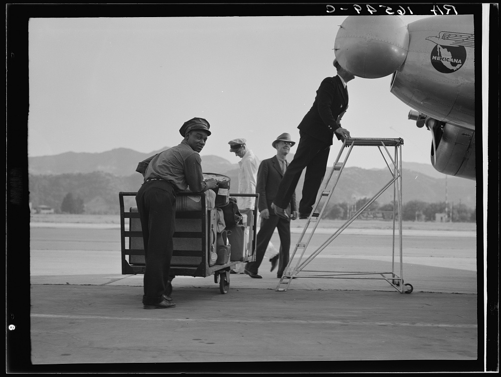 Department of Agriculture plant quarantine inspectors examining Pan American Airways plane from Mexico on its arrival at the Glendale Airport, California