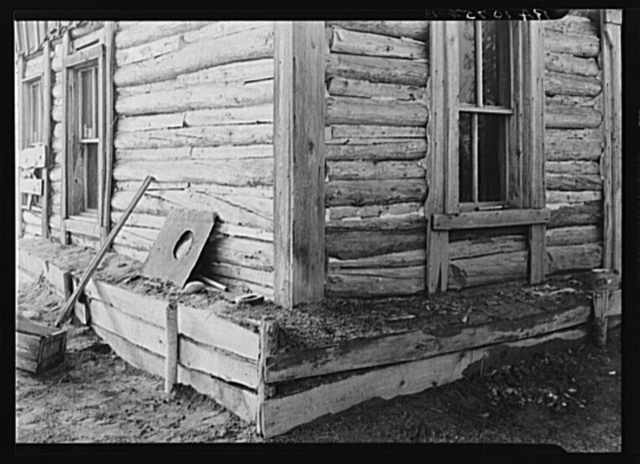 Detail of construction of a log cabin near Nelma, Wisconsin. Note the earth fill around base to keep in warmth in the winter. The space between the logs is usually filled with cement or mud. The windows are removed when a house is abandoned; people cannot build glass. This cabin is occupied by the Ingrahams and the Smallwoods; two families
