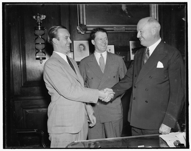 Farley meets new leader of young democrats. Washington, D.C. Aug 25. Newly elected president of the Young Democrats of America, Pitt. T. Maner, shakes hands with Jim Farley, while John P. Kohn, Jr., Maners campaign manager, looks on