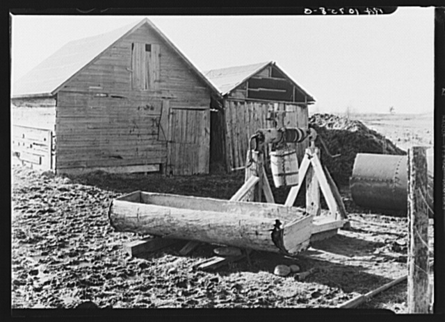 Farmyard of Matt Henry near Tipler, Wisconsin. A primitive water tank hollowed from a tree and a windlass still in operation. Farmers in this region have to make many of their own devices because of lack of funds to purchase manufactured equipment