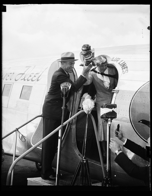 FIRST LADY CHRISTENS PLANE. WASHINGTON, D.C. MAY 17. MRS. FRANKLIN D. ROOSEVELT AND CAPT. EDDIE RICHENBACKER HOLDING THE BOTTLE OF CHAMPAGNE WHICH THE FIRST LADY USED TODAY IN CHRISTENING THE FLAGSHIP OF THE EASTERN AIR LINES WASHINGTON-NEW YORK RUN. UNDER THE NEW SCHEDULE WHICH STARTED TODAY, IT WILL BE A PLANE 'EVERY HOUR ON THE HOUR' FROM 8 A.M. TO MIDNIGHT FROM WASHINGTON TO NEW YORK. THIS WILL MAKE THE RUN THE MOST FEQUENT AIR TRANSPORT SERVICE IN THE WORLD