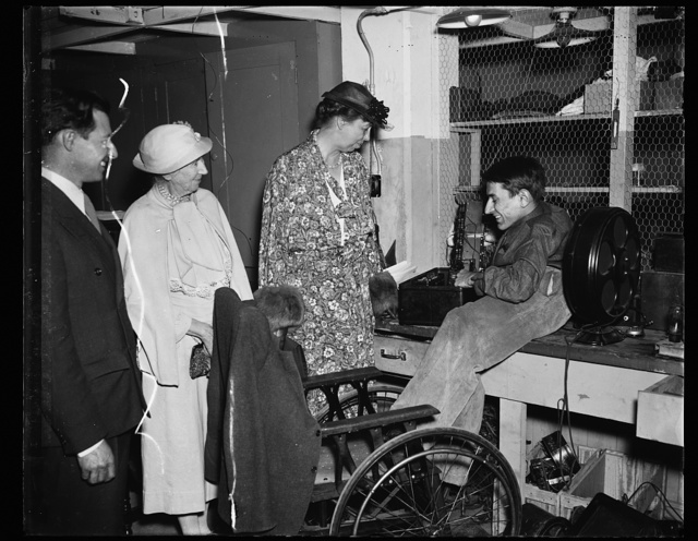 FIRST LADY VISITS GOODWILL INDUSTRIES. WASHINGTON, D.C. APRIL 20. MRS. FRANKLIN ROOSEVELT, AN HONORARY MEMBER OF THE COUNCIL OF GOODWILL INDUSTRIES, VISITED THE WASHINGTON AGENCY TODAY AND TALKED WITH THE AGED AND HANDICAPPED MEN AND WOMEN. SHE IS SHOWN WITH STANLEY WATERS, A CRIPPLED YOUNGSTER, WHOSE SPECIALTY IS THE REPAIRING OF RADIOS AND ELECTRICAL EQUIPMENT
