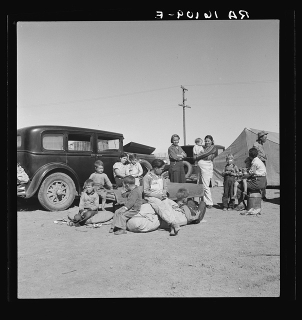 Four families, three of them related with fifteen children, from the Dust Bowl in Texas in an overnight roadside camp near Calipatria, California