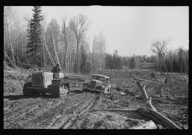 FSA (Farm Security Administration) photographer being pulled out of mud by tractor, near Littlefork, Minnesota