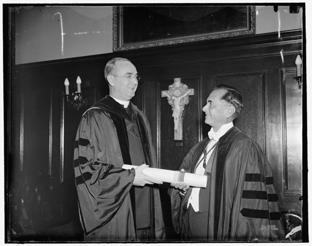 Georgetown University confers honorary degree on president of Philippines. Washington, D.C., April 19. President Manuel Queson of the Philippines receiving the honorary degree of Doctor of Laws from Georgetown University with the very Reverend Arthur O'Leary, President of the School, conferring the honor. The presentation was made at Founder's Day exercises, 4/19/1937