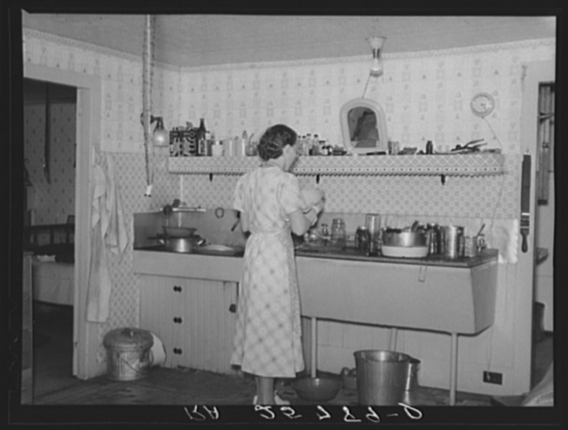Hired girl washing dishes on the McNally farm. Kirby, Vermont